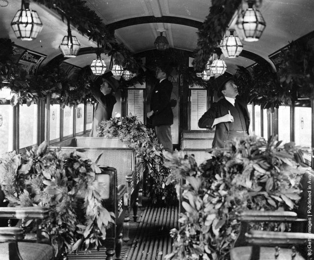 1920: The interior of a tube train decorated with foliage for the Christmas Season.