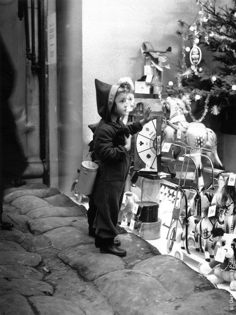 39: A seasonably attired young shopper climbs on to the sandbags to get a closer look at the toys in a shop window in the West End of London