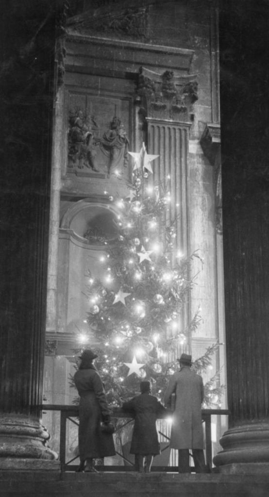 1938: 1938: A family looks at the sparkling lights on the Christmas tree at St. Paul's Cathedral, London
