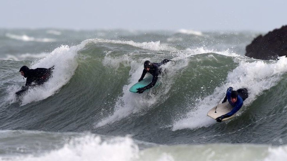Body boarders ride the stormy waves at Broad Haven, Pembrokeshire, Wales
